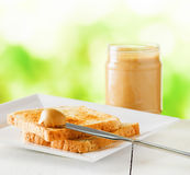 Jar of peanut butter and toasts on nature background Stock Image