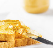 Jar of peanut butter and toasts on white table Royalty Free Stock Photo