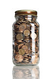 Jar of pennies. On a reflective tabletop Stock Photography