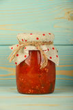 Jar of pepper salad at vintage wood surface Stock Images