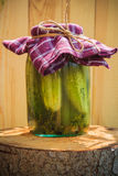 Jar pickled cucumbers wooden stump Stock Photography