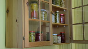 Jar pickled vegetable. Girl from a kitchen dresser takes two jars of pickled peppers and small tomatoes stock video footage