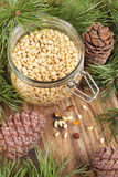 Jar with pine nuts on a rustic wooden table Royalty Free Stock Image