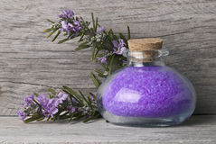 A jar with purple bath salts. A jar with rosemary bath salts with some rosemary branches with flowers Royalty Free Stock Photography