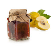 Jar of quince jam with ginger and fresh quince. Fruit isolated on white background Stock Photos