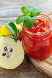 Jar with quince jam and a sprig of mint. Jar with quince jam and sprig of mint on an old table Stock Photos