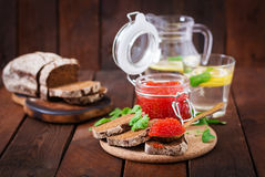 Jar with red caviar and bread Royalty Free Stock Image