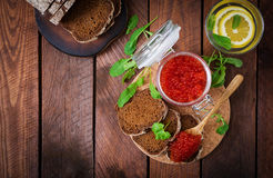 Jar with red caviar and bread on wooden background Royalty Free Stock Images