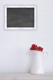 A jar with red roses on a white wooden shelf. Next, a blackboard. Stock Photos