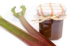 Jar of rhubarb jam with stalks of fresh rhubarb Royalty Free Stock Image