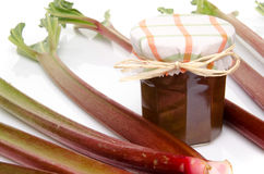 Jar of rhubarb jam with stalks of fresh rhubarb Royalty Free Stock Image