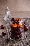 Jar with ribbon and fresh cherries on wooden table. Stock Photos