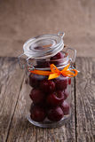 Jar with ribbon and fresh cherries on wooden table. Royalty Free Stock Photo