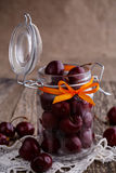 Jar with ribbon and fresh cherries on wooden table. Royalty Free Stock Photos