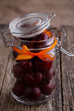 Jar with ribbon and fresh cherries on wooden table. Stock Photography