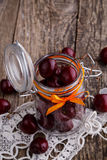 Jar with ribbon and fresh cherries on wooden table. Royalty Free Stock Photography