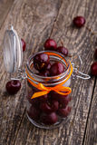 Jar with ribbon and fresh cherries on wooden table. Royalty Free Stock Images