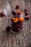 Jar with ribbon and fresh cherries on wooden table. Royalty Free Stock Image