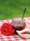 Jar of the rose jam. Jar of rose jam and one rose on the napkin Royalty Free Stock Photo