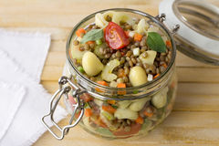 Jar with salad of vegetables, pasta and lentils Royalty Free Stock Images