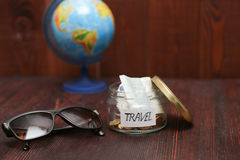 Jar with savings for travel, brown sunglasses, globe at background Stock Photos