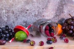 Smoothie jar shape fruits. Grapes, raspberry, lime, dark background royalty free stock photos