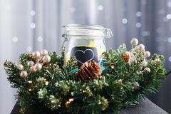 Jar with stickers and painted heart standing wreath in Christmas Royalty Free Stock Image
