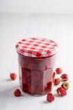 Jar of strawberry jam. Canned homemade strawberry jam with some fresh berries around it stock photo