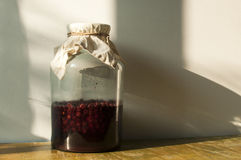 Jar with sugar soaked sour cherries Stock Image