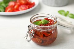 Jar with sun dried tomatoes on light table. Space for text royalty free stock images