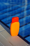Jar with sunscreen uv lotion in water of swimming Royalty Free Stock Images