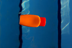 Jar with sunscreen uv lotion in water of swimming pool Royalty Free Stock Image