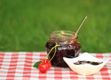 Jar of sweet cherry jam Stock Images