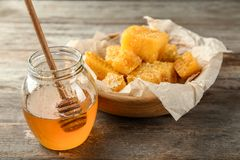 Jar with sweet honey and combs. On wooden table Stock Image