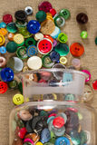 Jar of vintage buttons. A great variety of colorful vintage buttons spilling out of a jar, against a fabric background. Portrait orientation royalty free stock photography