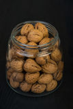 Jar of walnuts. Walnuts in a glass jar on a dark wooden background Royalty Free Stock Photography