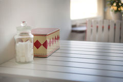 Jar with white sugar cubes and vintage box on the table. Stock Image