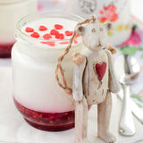 A Jar of Yoghurt with Raspberry Jam and a Teddy Bear Toy Leaning Stock Photo