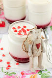 A Jar of Yoghurt with Raspberry Jam and a Teddy Bear Toy Leaning Over It Royalty Free Stock Photography