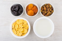 Jar of yogurt, corn flakes and dried fruits in bowls Stock Images