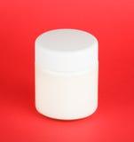 Jar with yogurt isolated on red background Stock Photo