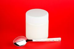 Jar with yogurt isolated on red background Royalty Free Stock Photography