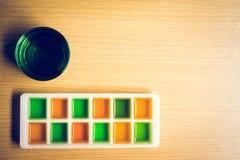 Jarabe anaranjado y verde con el vidrio de agua de soda verde en la tabla de madera Imagen de archivo libre de regalías