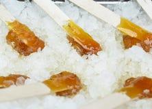 jarabe de arce caliente en un palillo en la nieve fotos de archivo libres de regalías