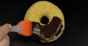 Jarabe de chocolate oscuro derretido delicioso que extiende por un buñuelo en fondo negro almacen de video