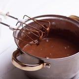 Jarabe de chocolate que se escapa de la herramienta de la cocina en la tabla Imagen de archivo libre de regalías