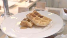 Jarabe de colada del caramelo en las galletas belgas en la placa blanca Galletas cocidas dulces con la miel para la ma?ana tradic metrajes