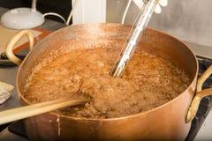 Jarabe de ebullición del azúcar en la cacerola de cobre con el termómetro y la cuchara grande Color de Brown debido a la evaporac Fotos de archivo libres de regalías