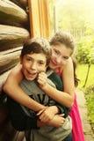 Jardín adolescente de la sonrisa del abrazo de la muchacha del muchacho de los hermanos Foto de archivo libre de regalías