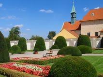 Jardín ajardinado hermoso por completo de flores florecientes hermosas y árboles y fuente ornamentales Imágenes de archivo libres de regalías